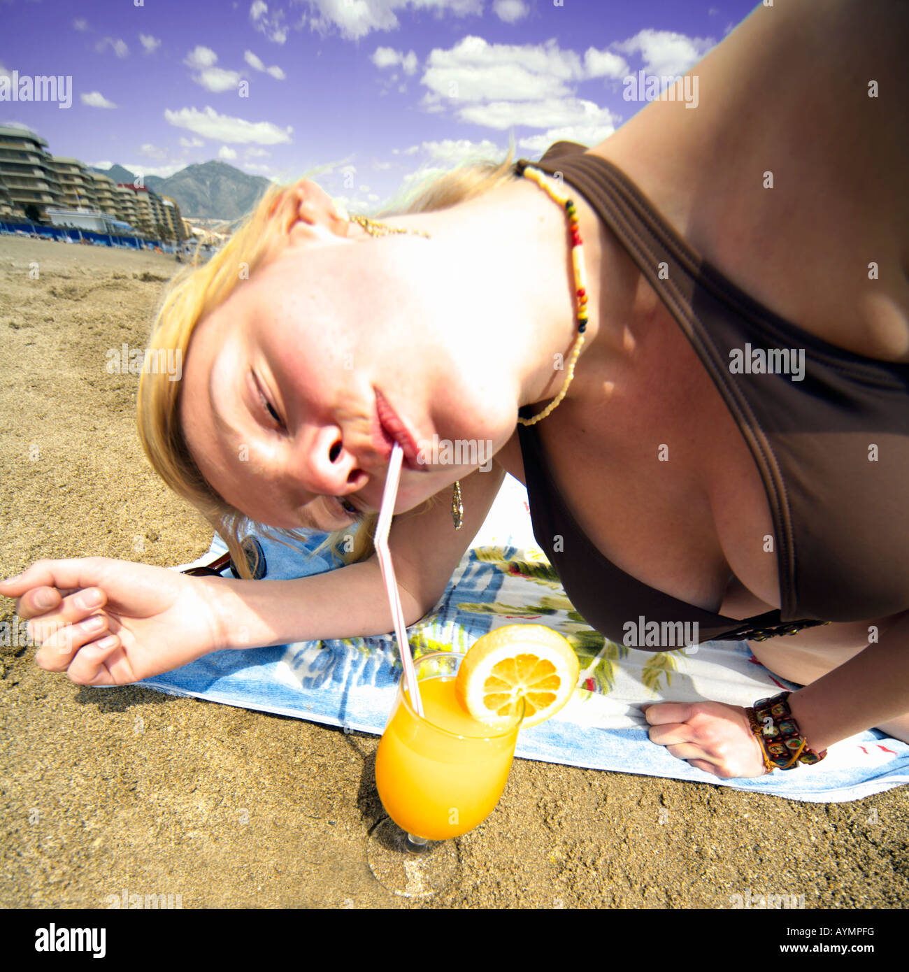 d2623b99501144 Beautiful happy young woman on Fuengirola beach, Costa del Sol, Spain,  drinking orange juice