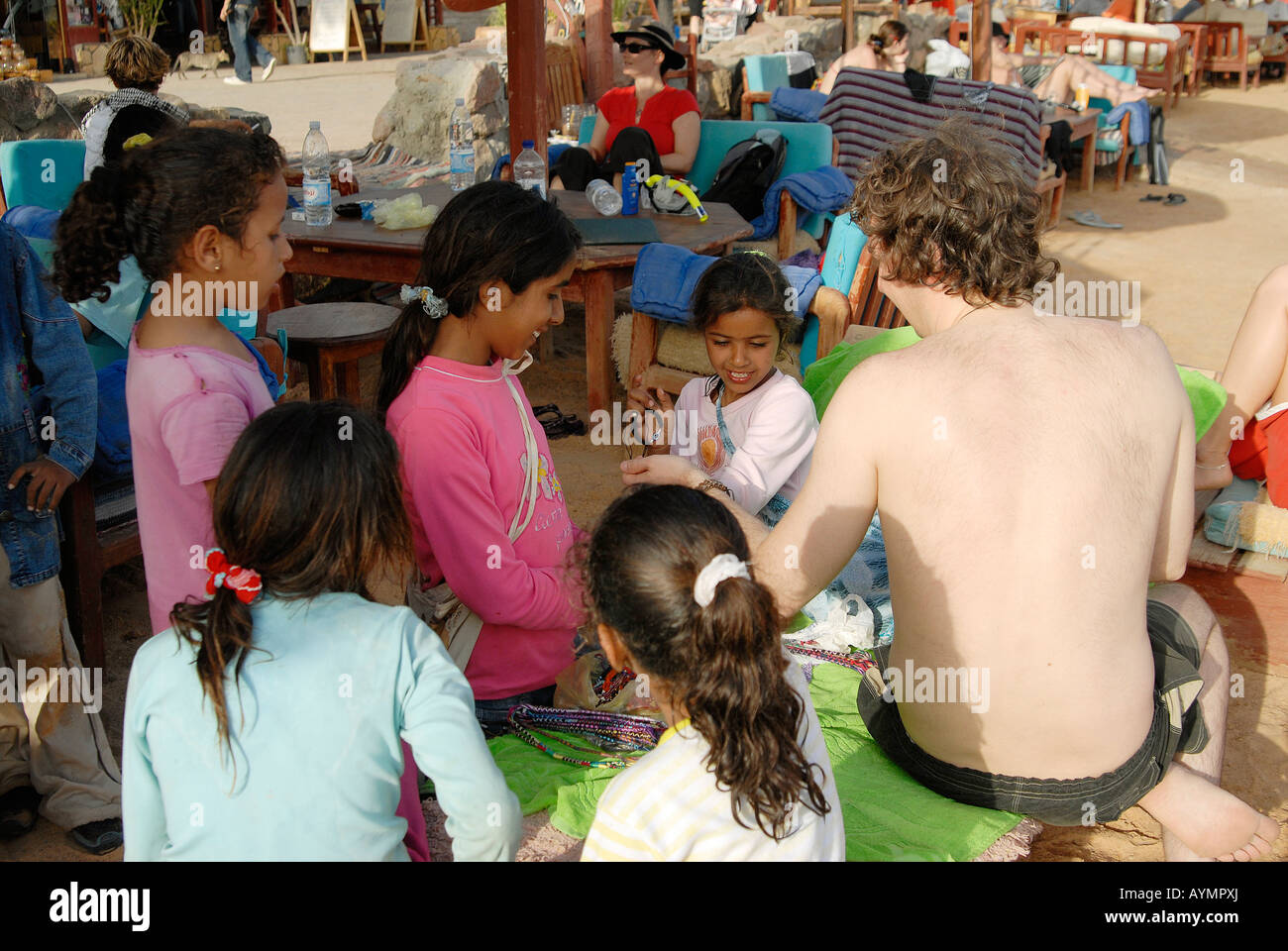 Bedouin children are selling bracelets to a white tourist in Dahab, Egypt - Stock Image