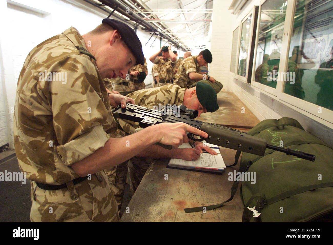 Royal Marines from HQ 3 Commando Brigade in Plymouth draw their weapons from the armoury - Stock Image