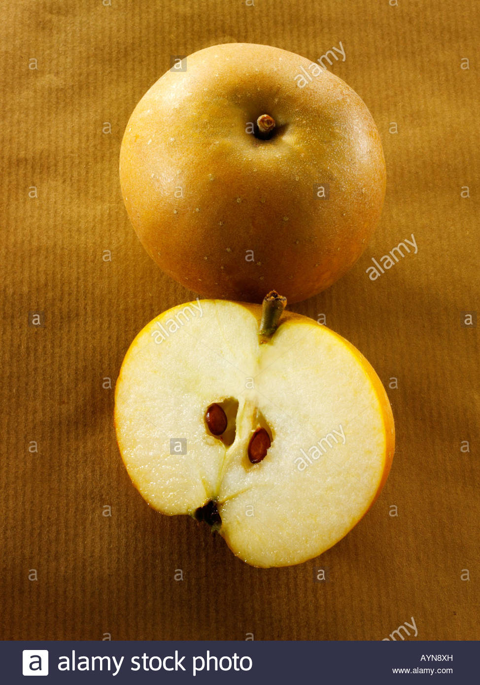 organic Russet apple cut and whole - Stock Image