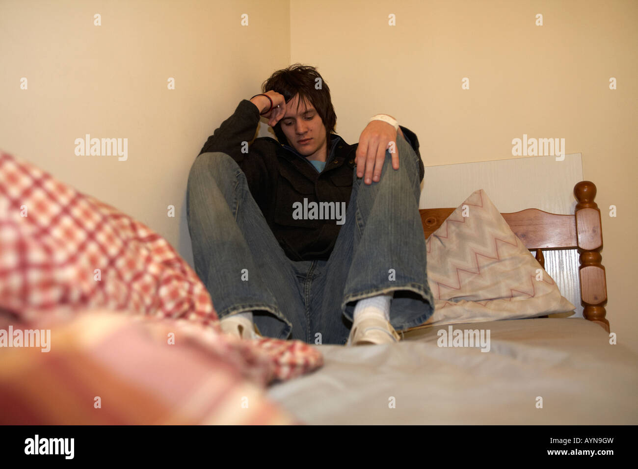 young dark haired teenage man sitting at the far end of his bed in an untidy bedsit bedroom curled up back to the - Stock Image