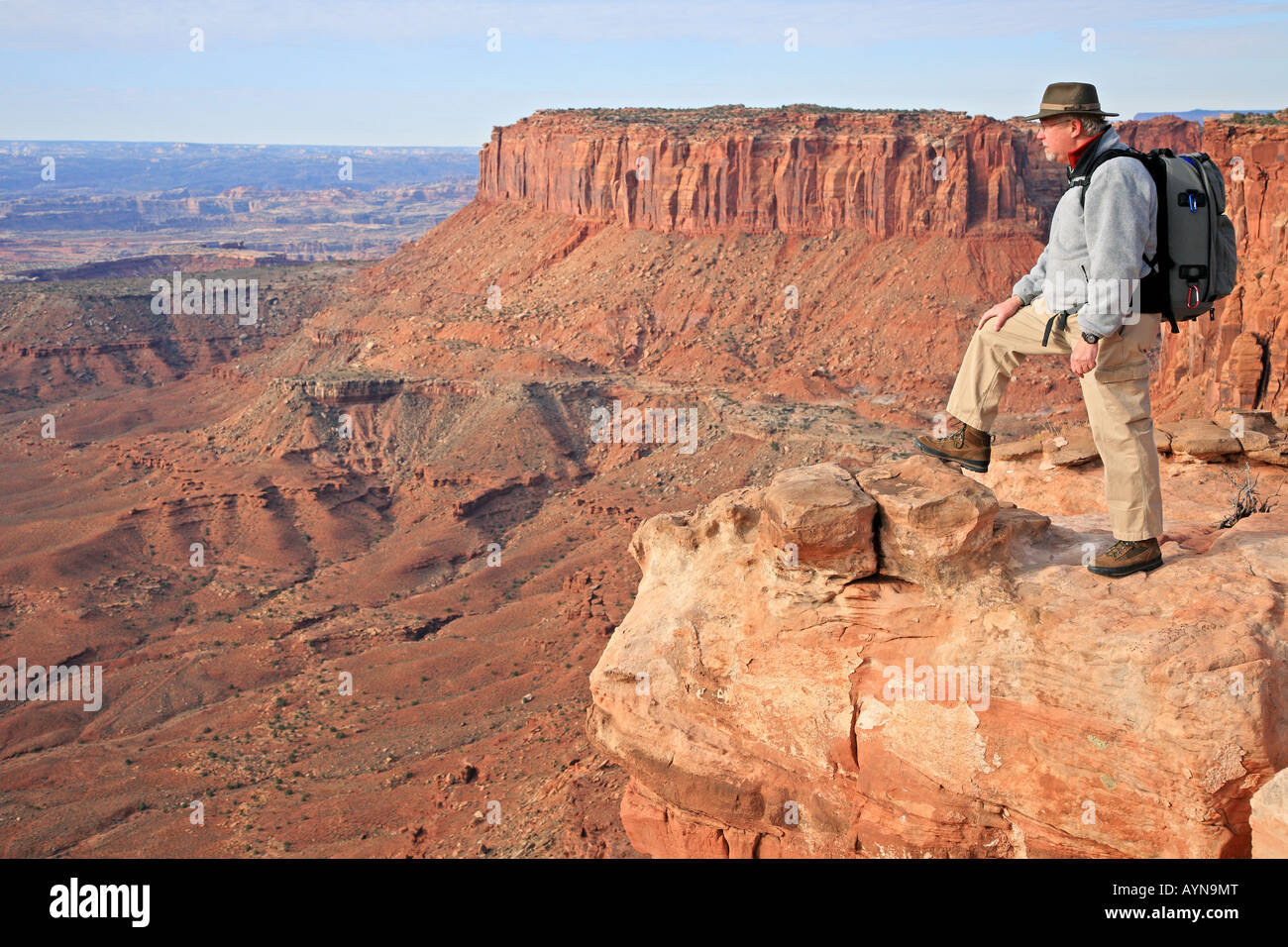 Hiker camper canyon rock sandstone pack man cliff over look view scenic Canyonland Park Utah Grand View - Stock Image