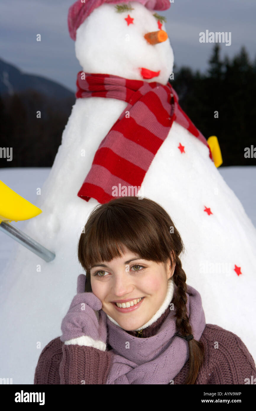 Brunette young woman sitting in front of a snowman, portrait - Stock Image