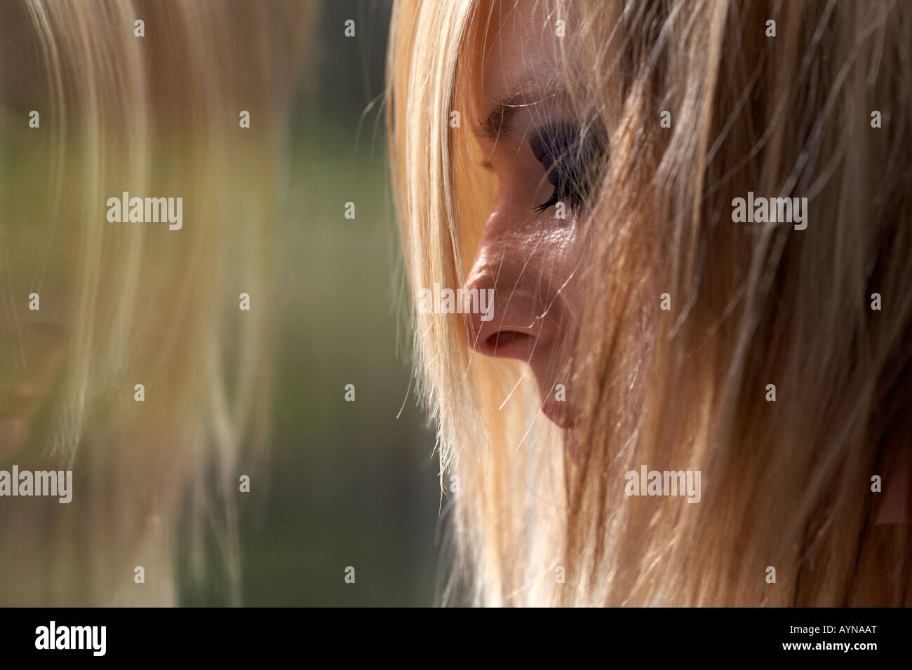 young blonde haired teenage woman crying in front of dirty window with reflection illustrating student mental health - Stock Image