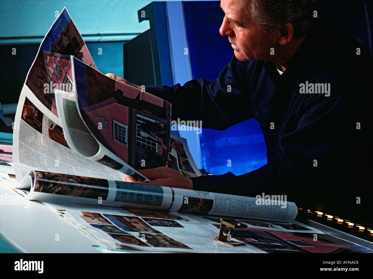 Caucasian pressman reviewing offset proof sheets in printing plant - Stock Image