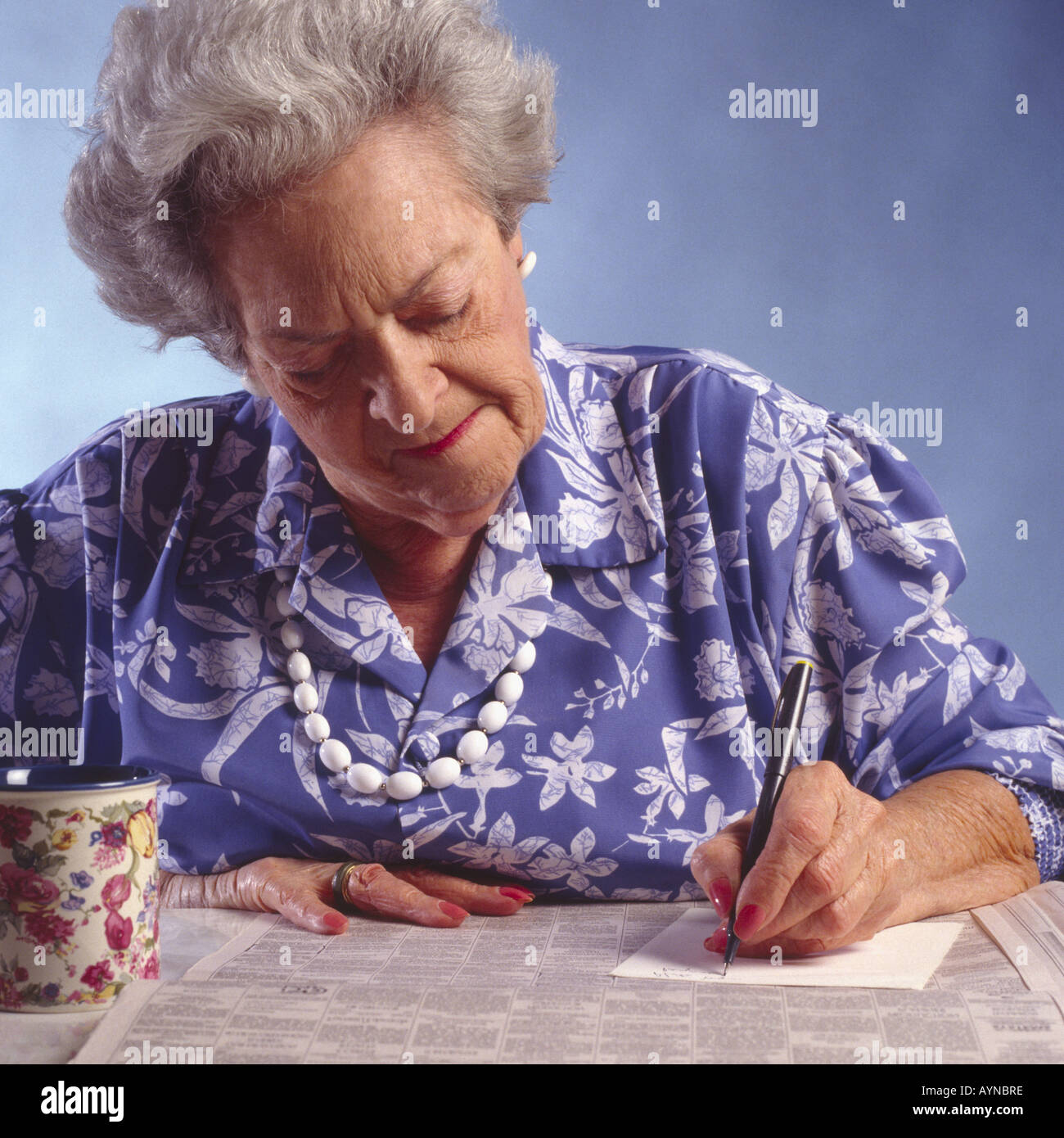 elderly woman with newspaper classified section seated at table taking notes - Stock Image