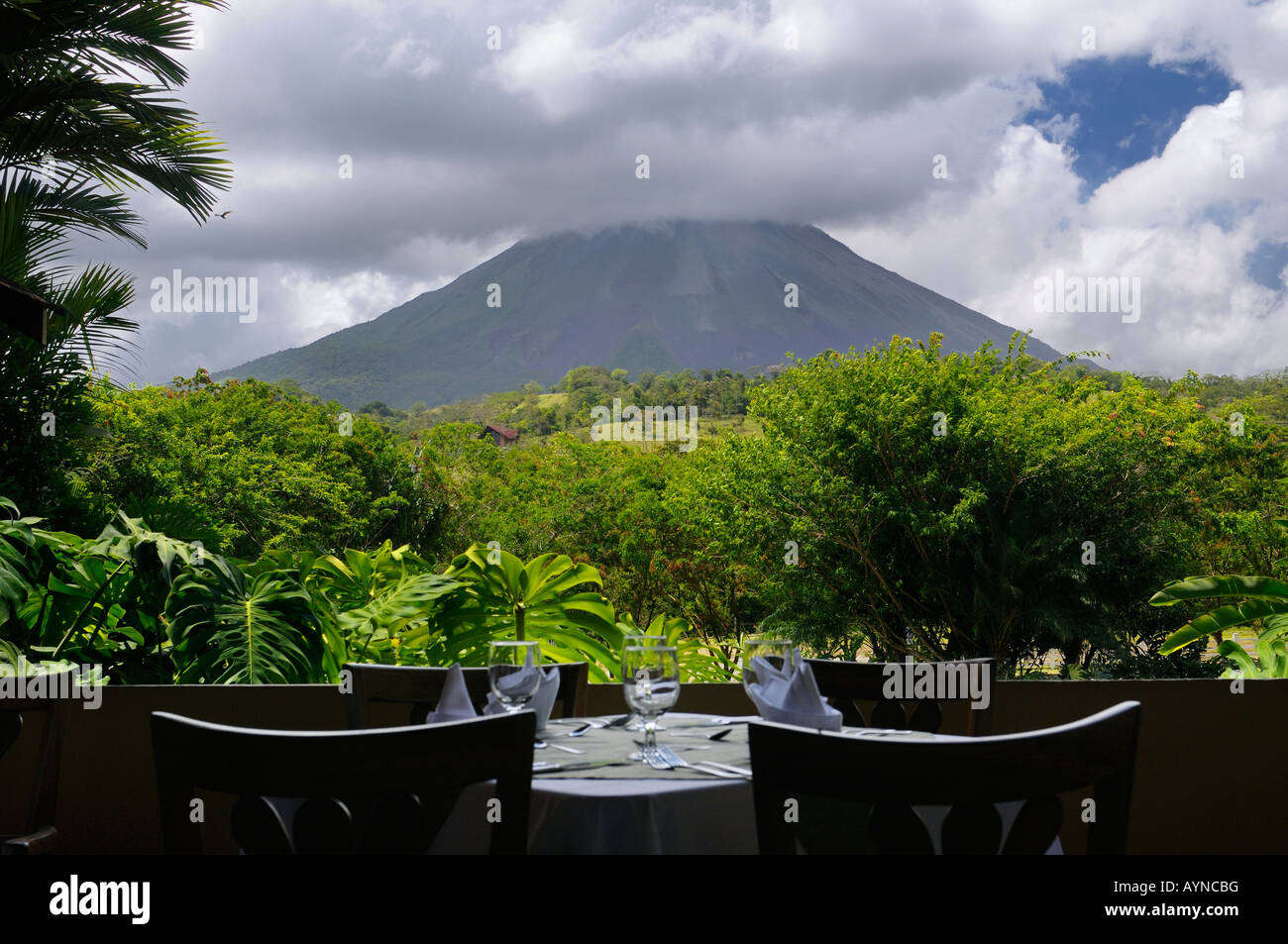 Arenal Volcano seen from the restaurant tables at the Paraiso Resort and Spa - Stock Image