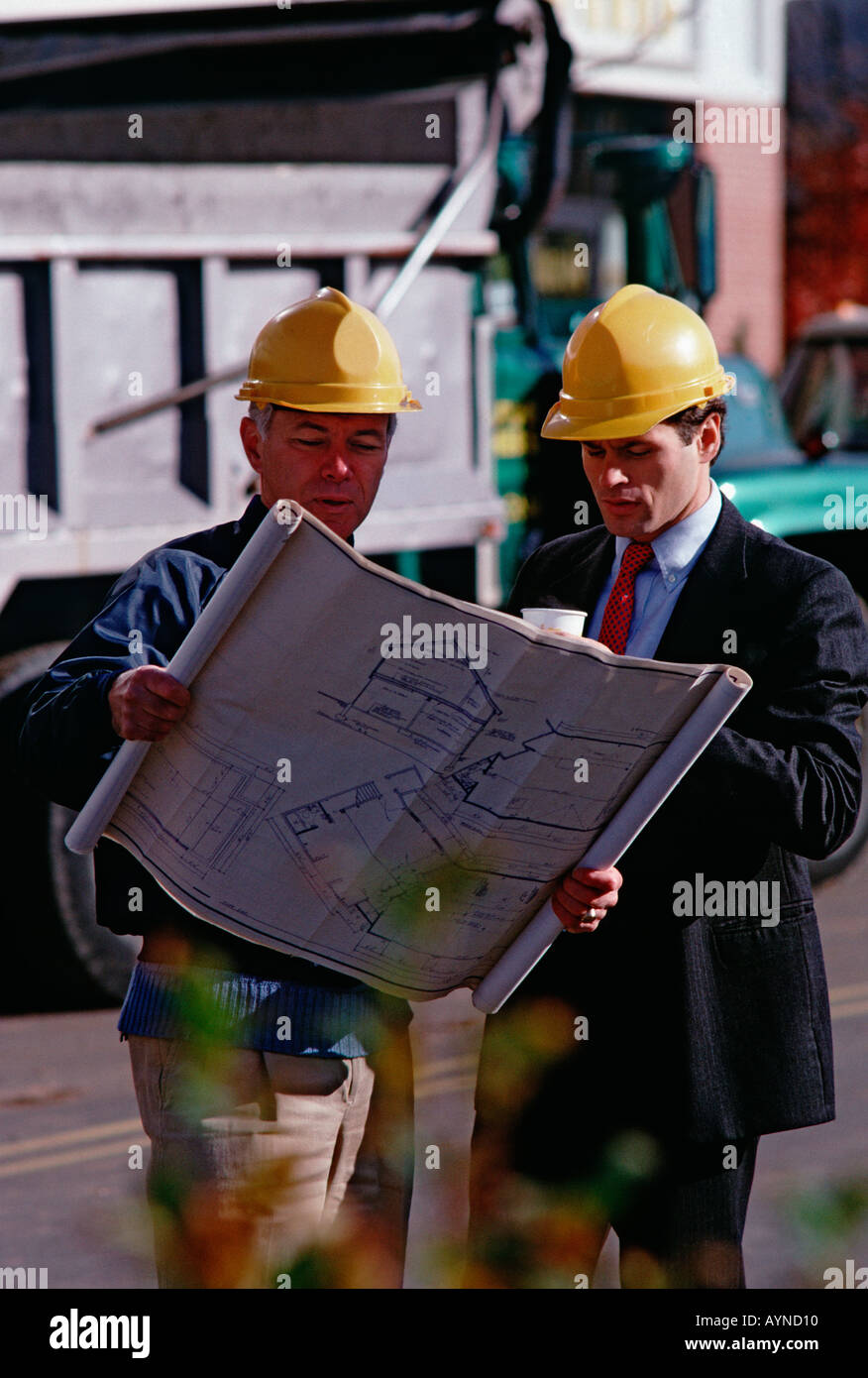 Caucasian architect and construction foreman on the job site wearing hardhats and looking at blueprints - Stock Image
