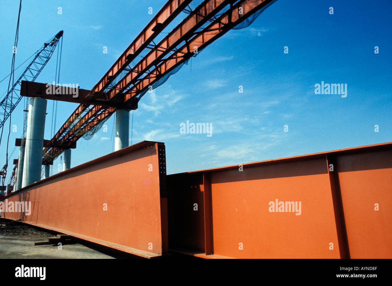 Steel girder staged and waiting to be put in place for an overhead highway construction project - Stock Image