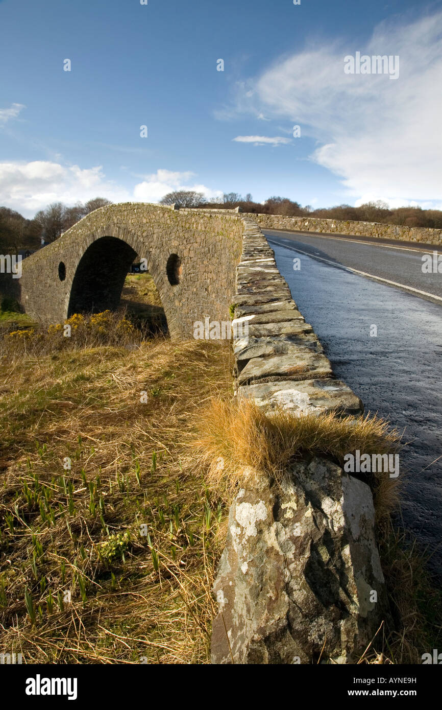 is more correctly known as Clachan Bridge. Built in 1792, its graceful arch crosses to Seil Island. - Stock Image