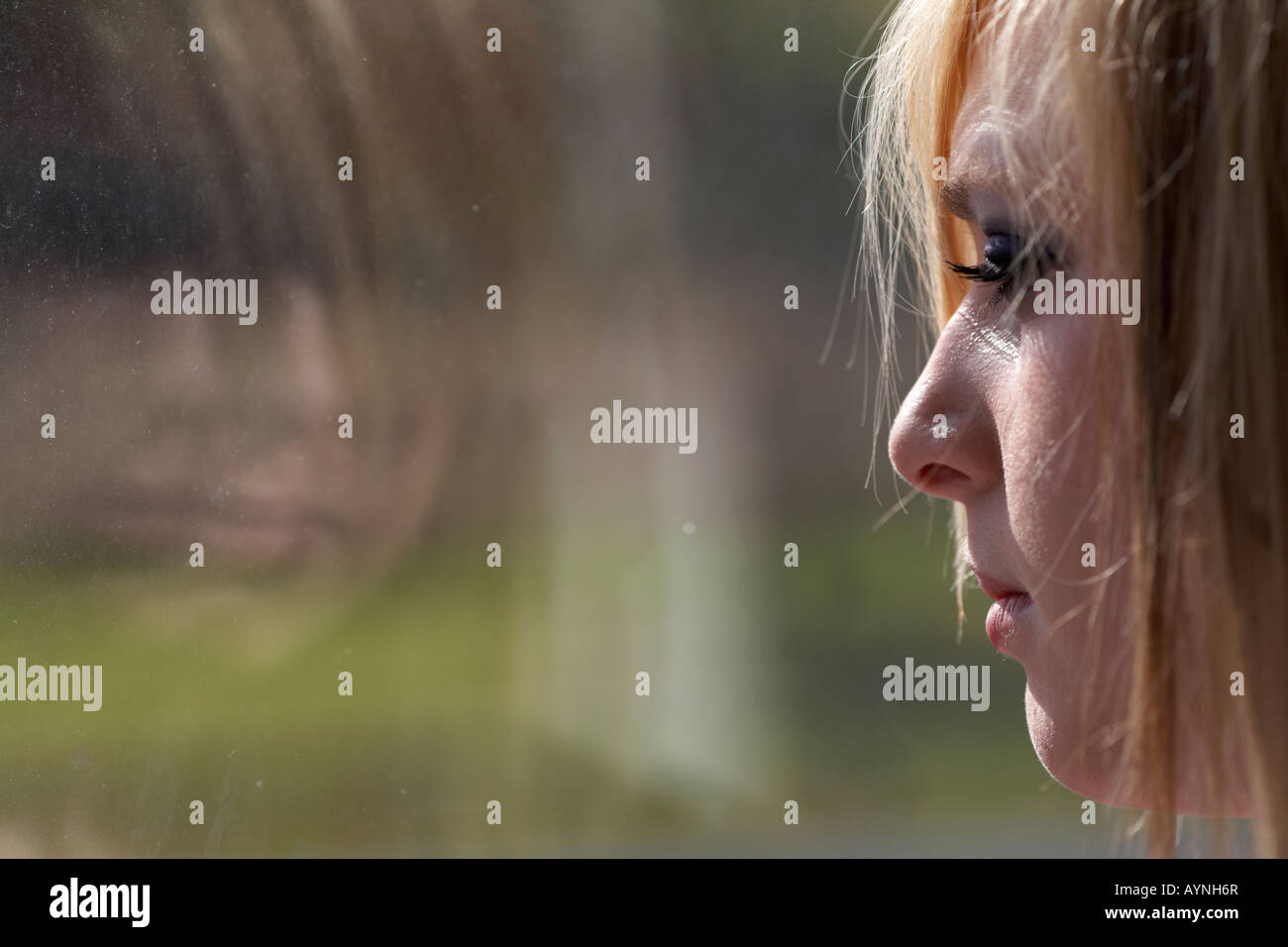 young blonde haired teenage woman staring blankly out through dirty window with reflection - Stock Image