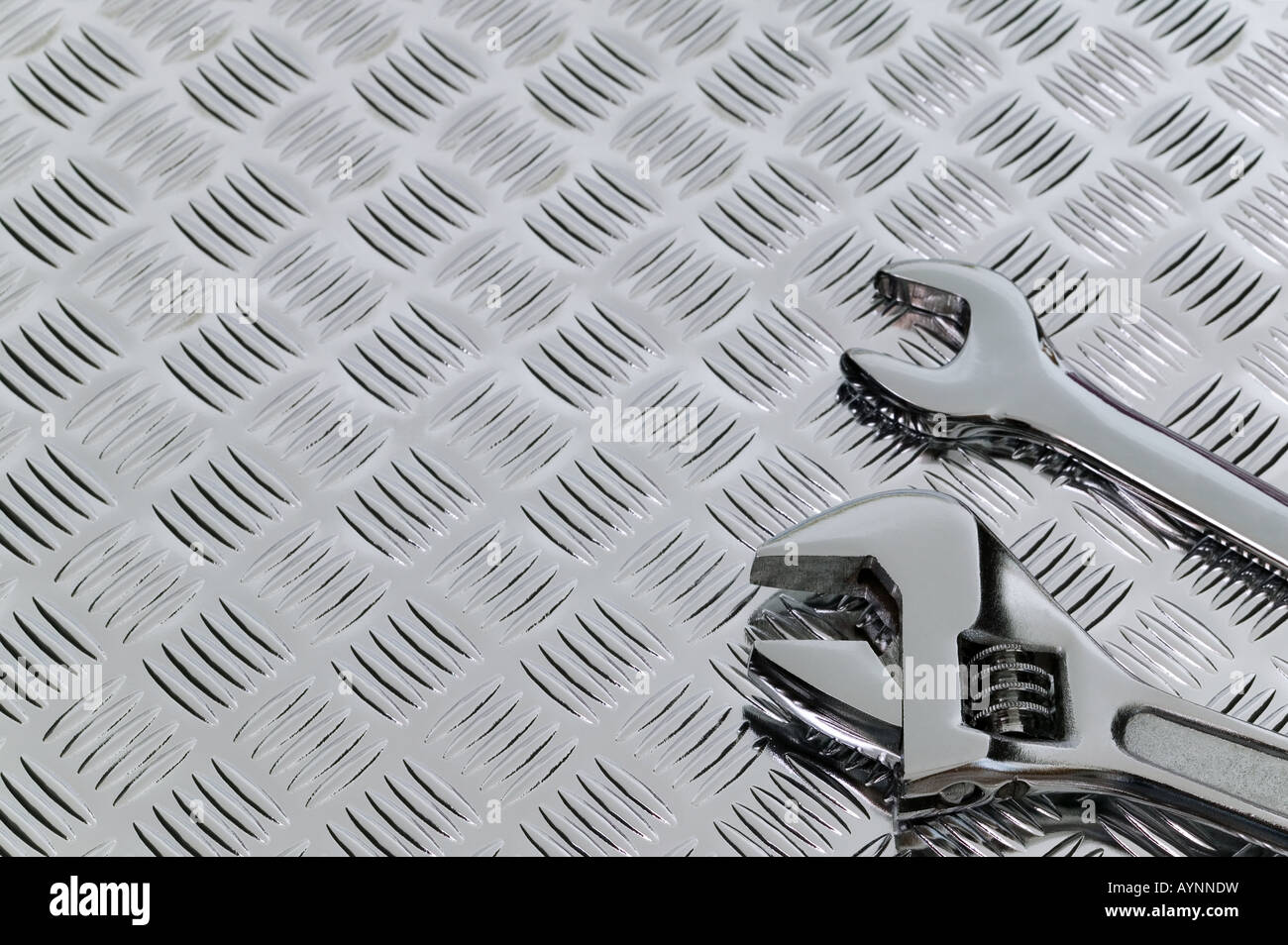 Mechanical image of two spanners on a checkerplate background - Stock Image
