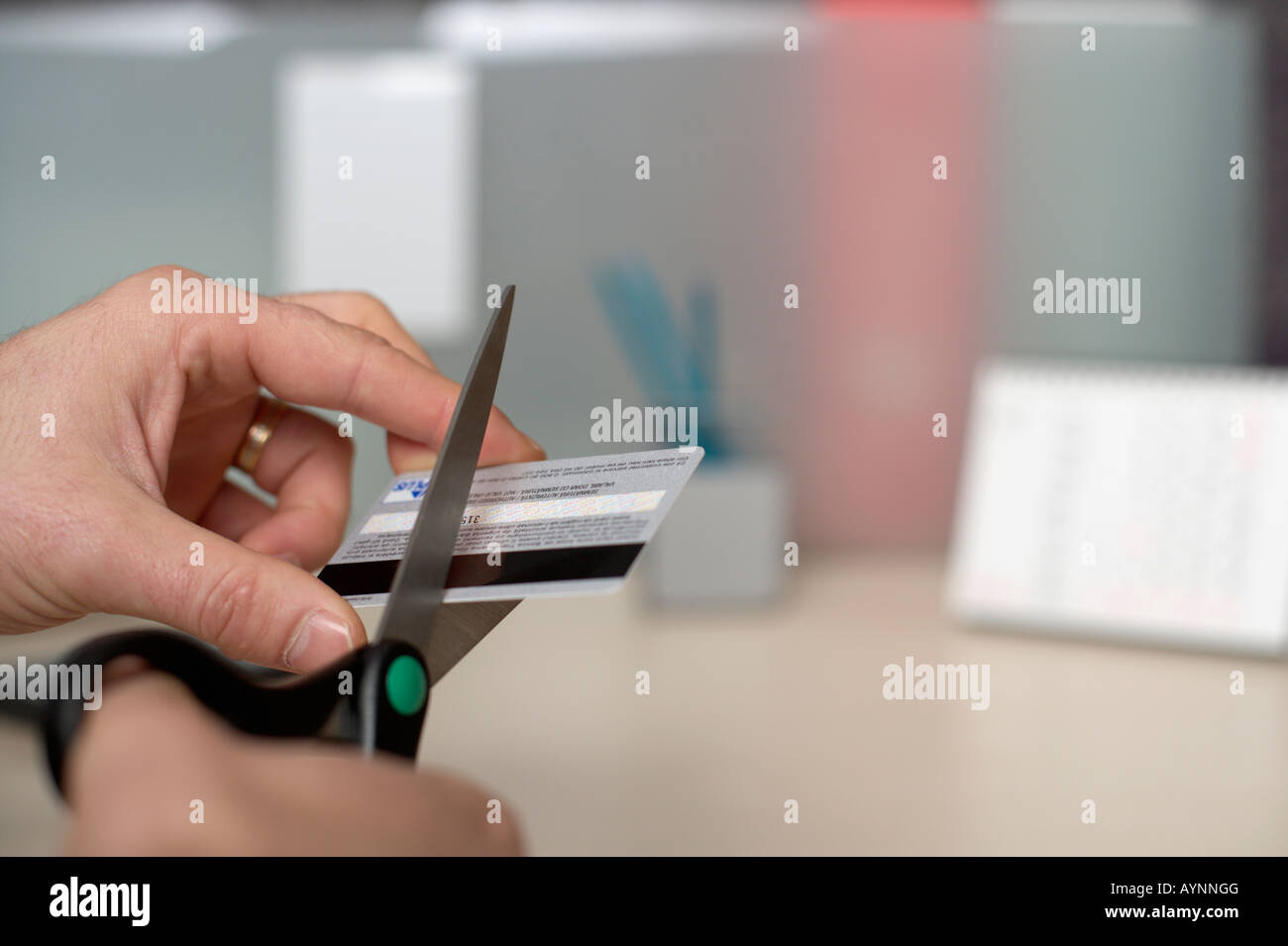 Businessman cutting his credit card in two - Stock Image