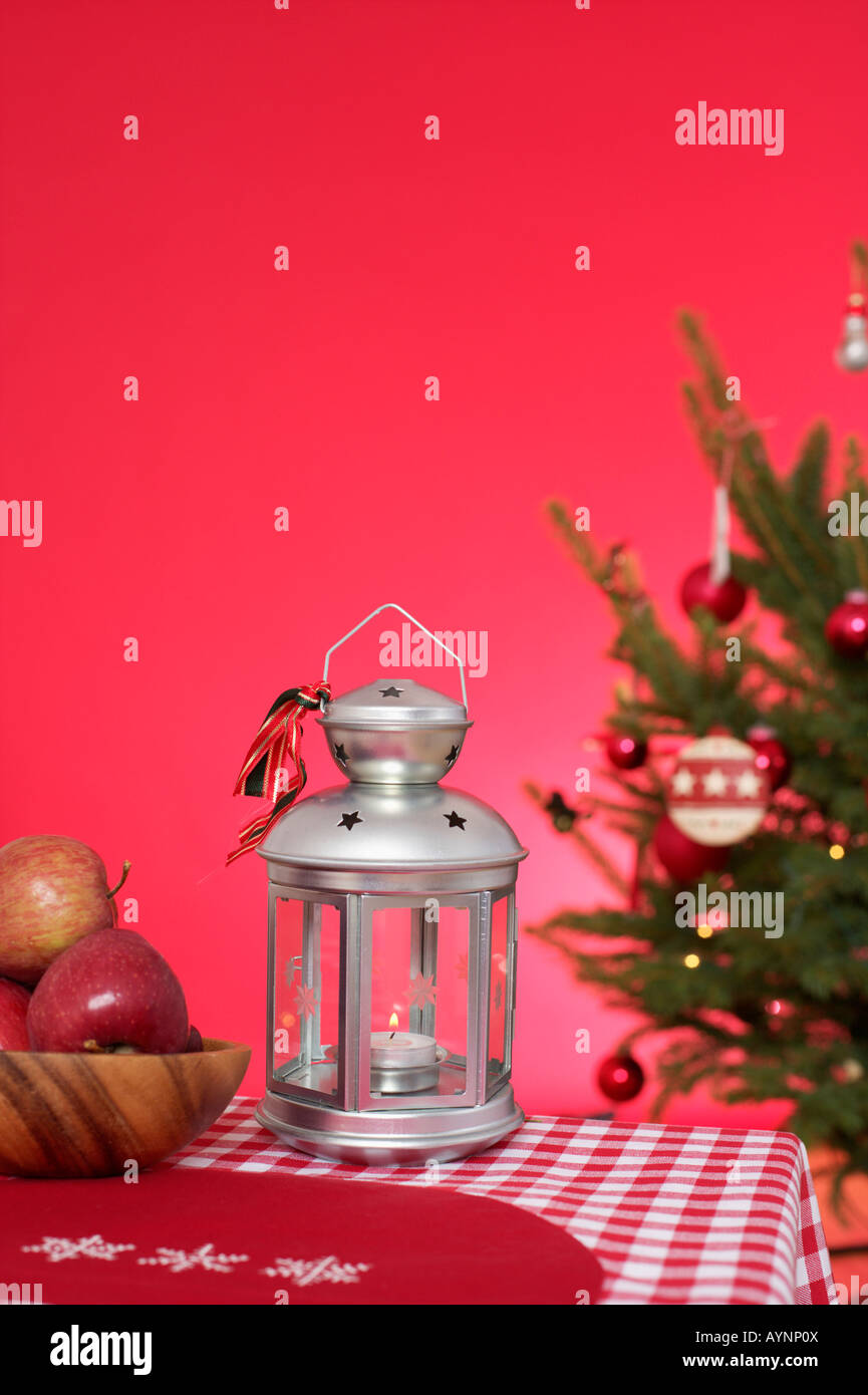 Christmassy decorated table with lantern, Christmas tree in background Stock Photo