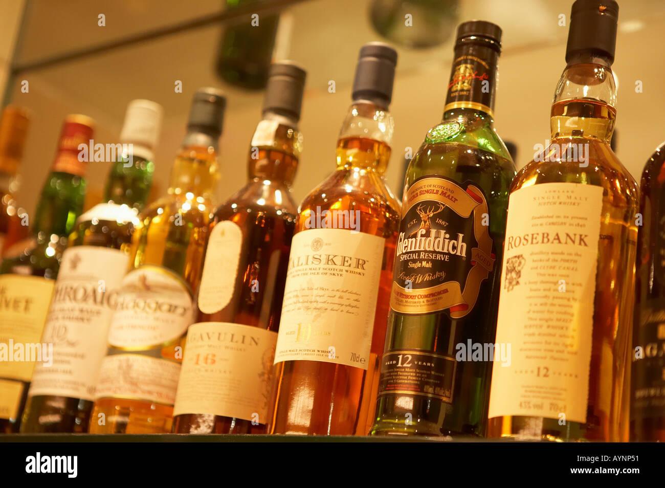 SELECTION OF SCOTCH WHISKY BOTTLES ON GLASS SHELVES IN BAR Stock ...