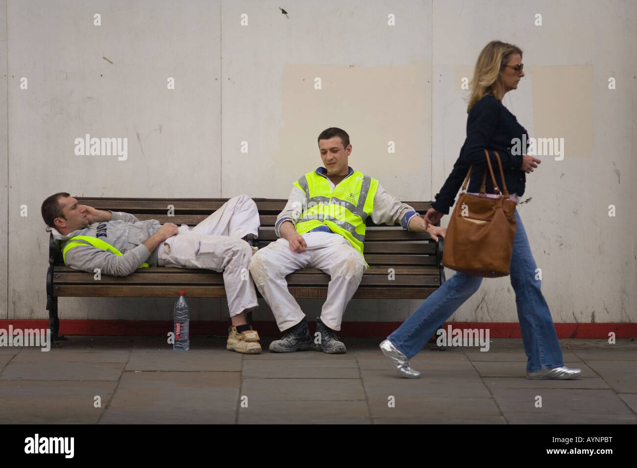 Resting Polish construction workers and passer by in Kings Road Chelsea London SW3 - Stock Image
