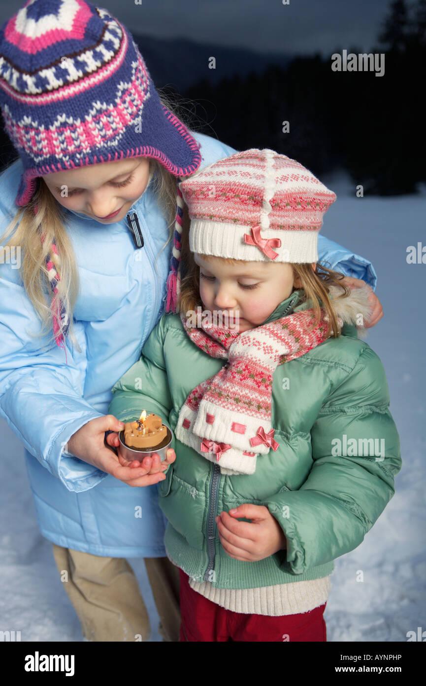Two girls wearing warm clothing holding a burning candle - Stock Image