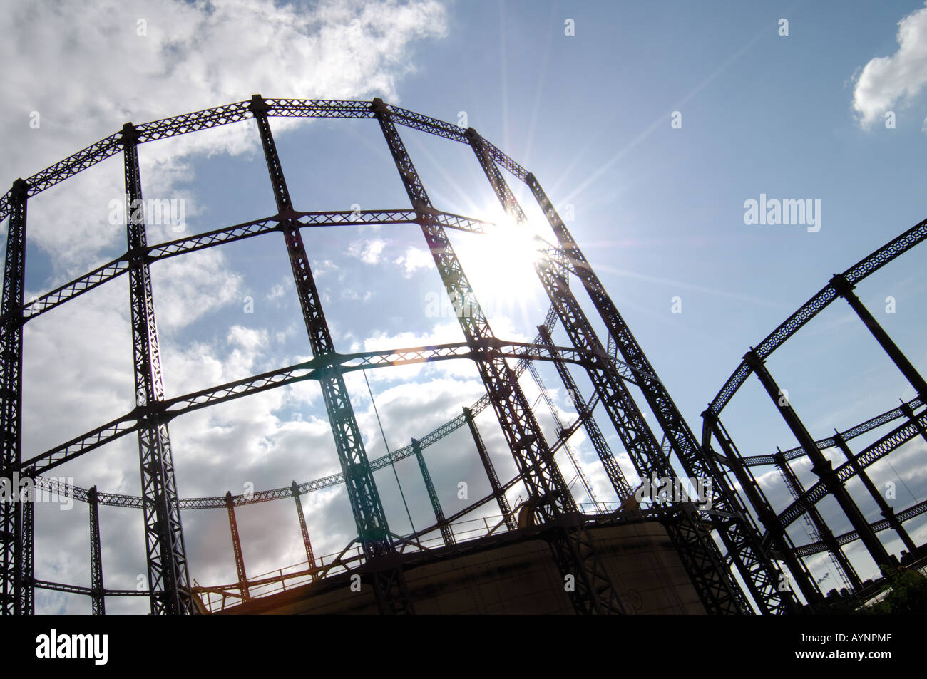 London Gas towers standing blackly against a blue cloudy sky lit up by  flared sunlight Stock Photo