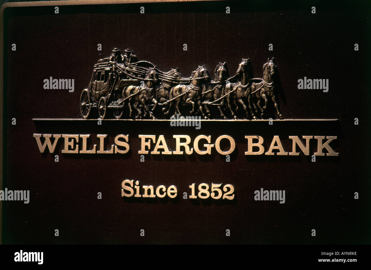 Gold lettering on a black background and an illustration of a stagecoach drawn by a team of horses marks the Wells Fargo Bank which was founded in 1852 as a natural progression from the company s gold shipping and storage services San Francisco - Stock Image