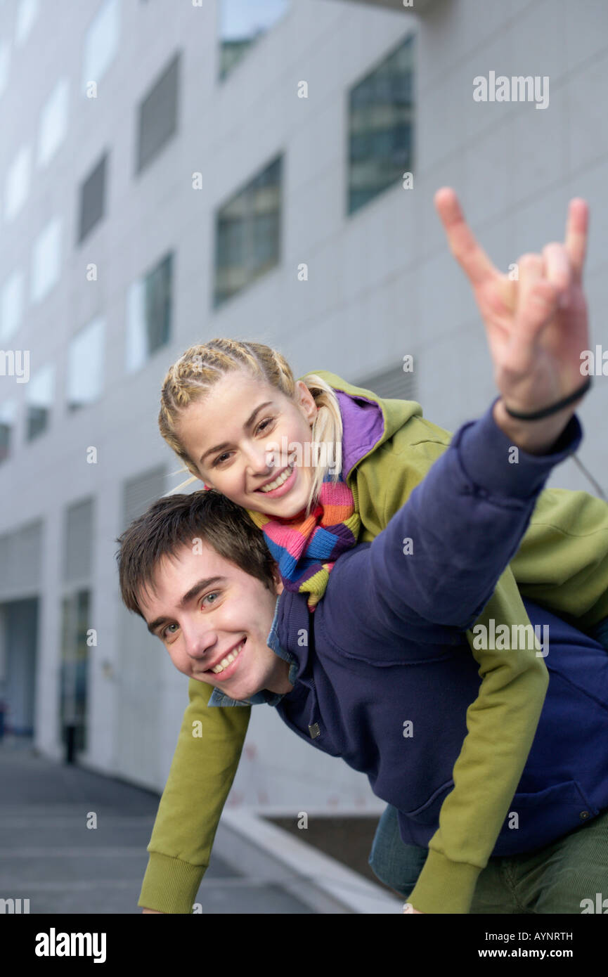 Young man giving young woman piggyback, portrait - Stock Image