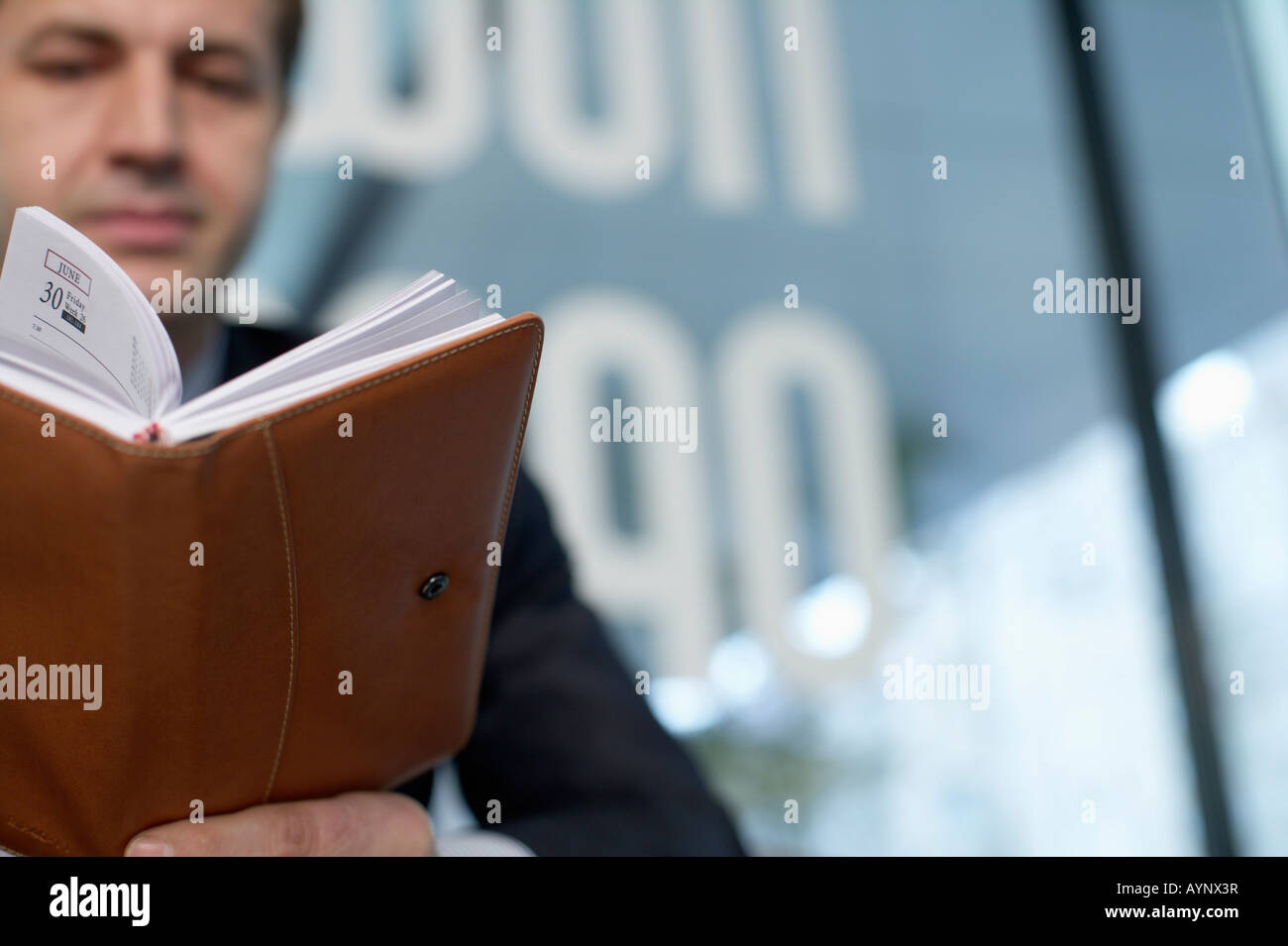 Businessman looking in his diary - Stock Image