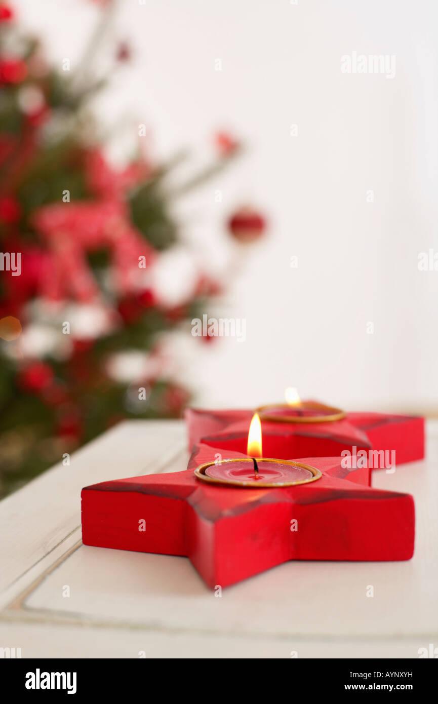 Star shaped candleholder with burning tea candles - Stock Image