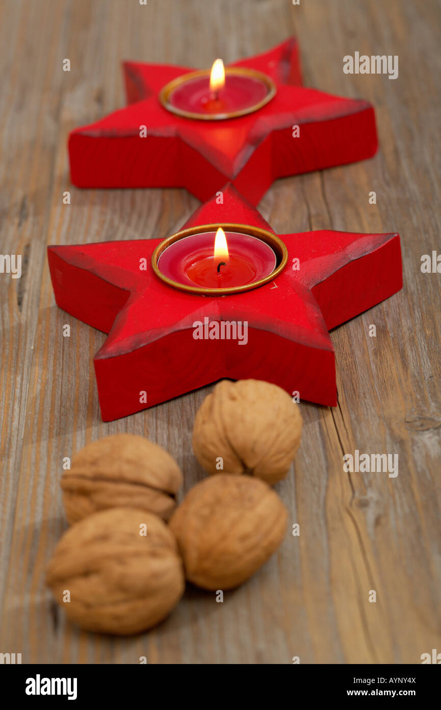Star shaped candleholder with burning tea candles and walnuts - Stock Image