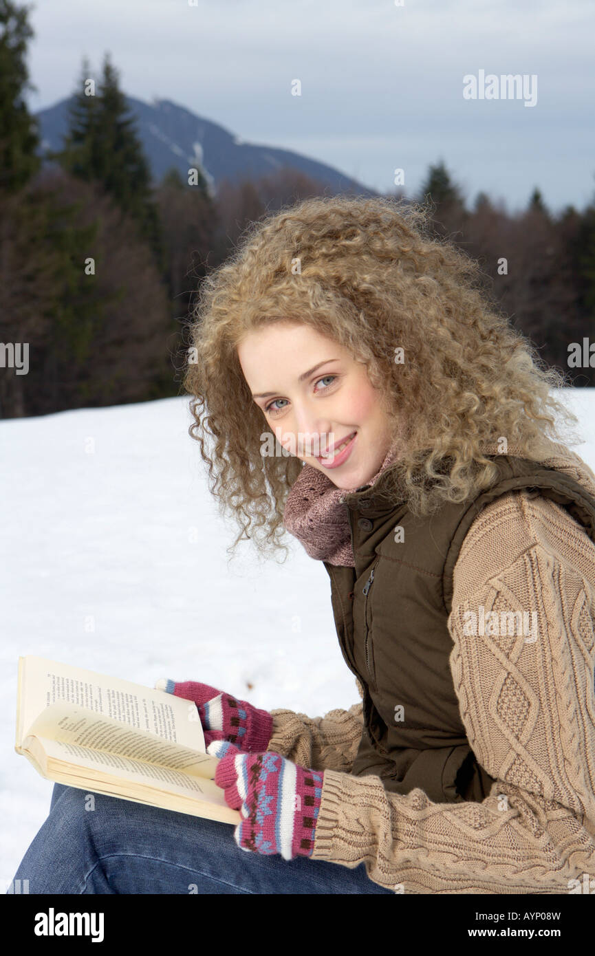 Young blonde woman with curly hair is reading a book in winterly landscape - Stock Image