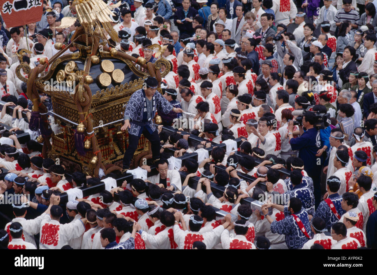 JAPAN Honshu Tokyo Religion Buddhism Men carrying Mikoshi Shrine through  crowds of people in street during a festival - Stock Image