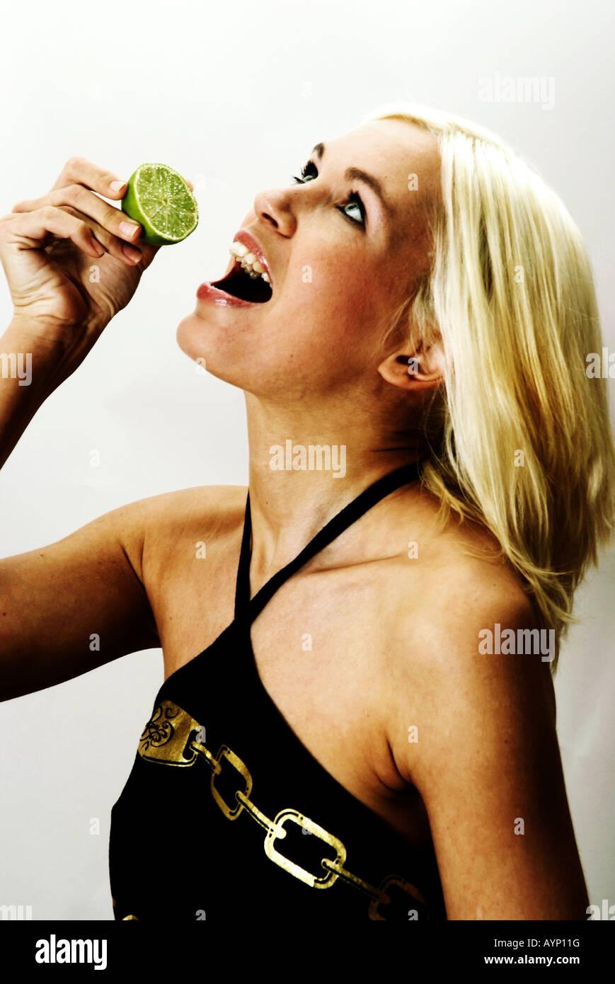 Blonde Woman with piece of Lemon | Blonde Frau mit einer halben Limone Stock Photo
