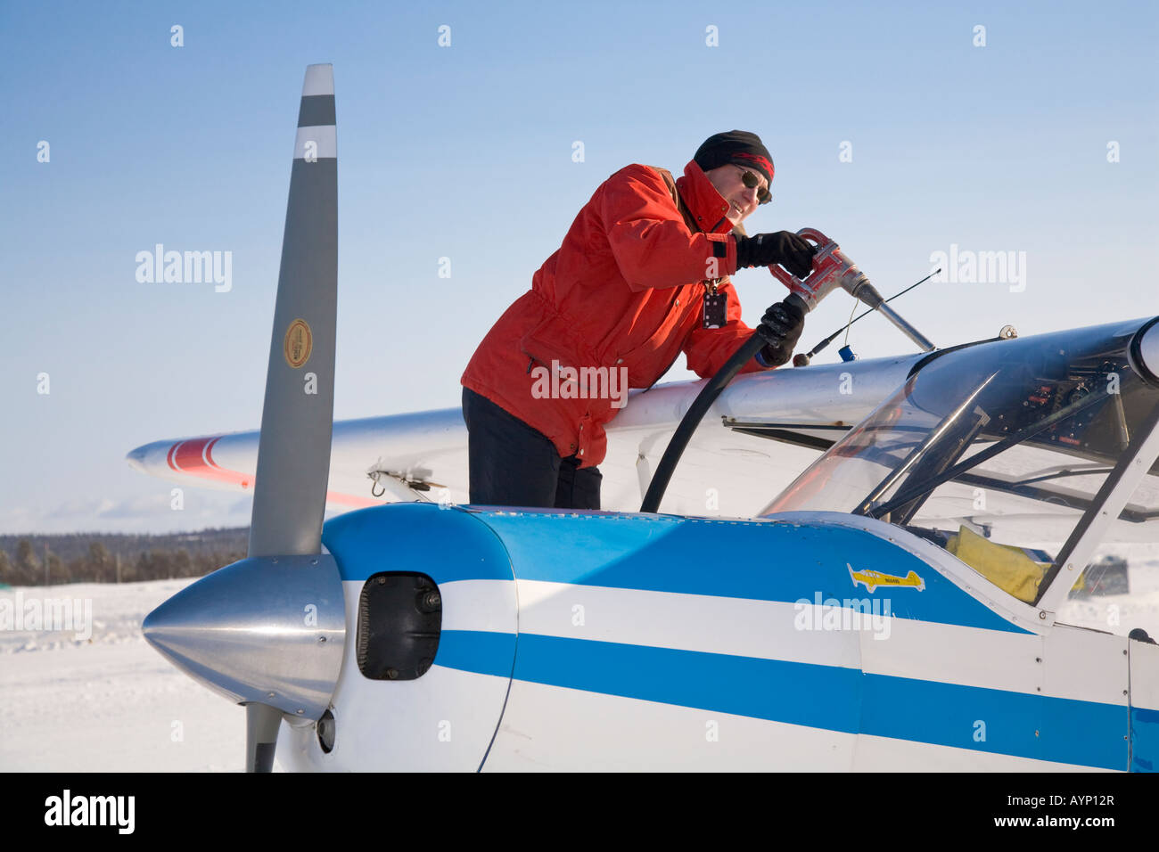 Pilot Olle Norberg refuelling his Piper PA18-150 Super Club on the Kiruna airport - Stock Image