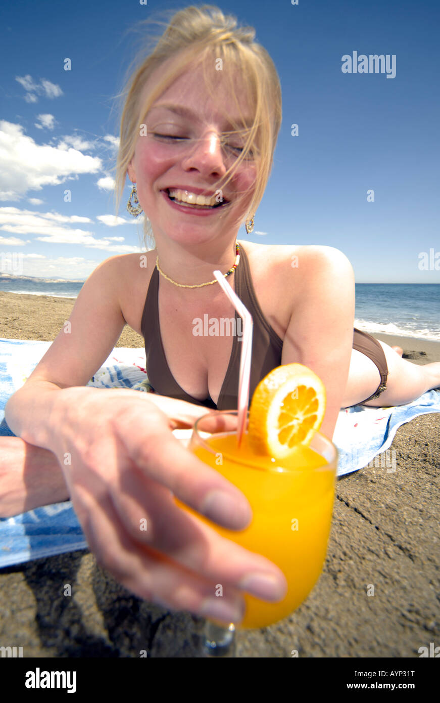 87374306ee2f93 Beautiful young woman with drink laughing on Fuengirola beach, Costa del Sol,  Spain