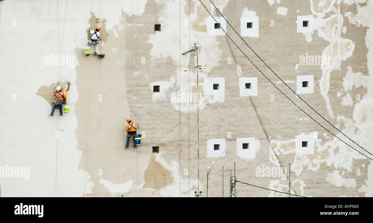 painters suspended from ropes paint exterior wall in Caravaca de La Cruz,Spain - Stock Image