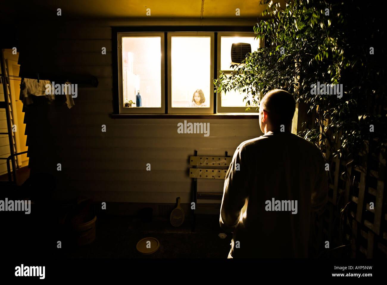 Man watches woman through kitchen window at night - Stock Image