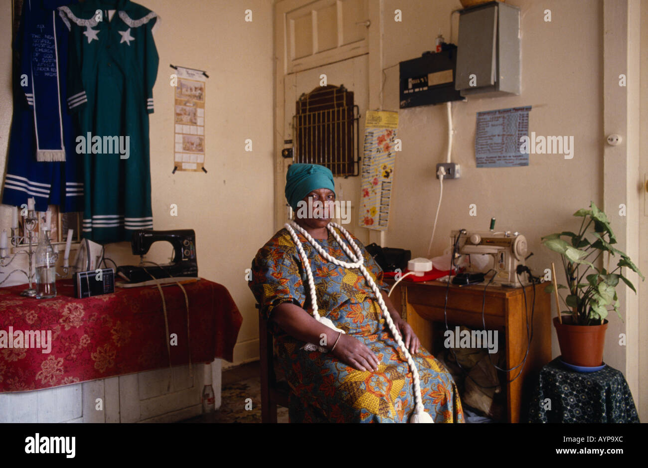 SOUTH AFRICA Guateng Johannesburg Portrait of female Zionist uniform maker in home workshop sitting beside sewing machine - Stock Image