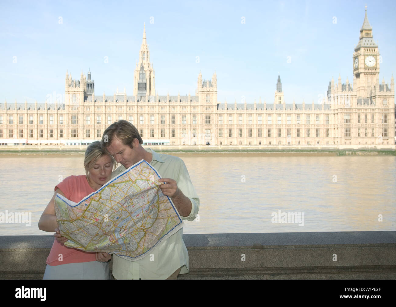couple looking at map together opposite houses of parliament - Stock Image