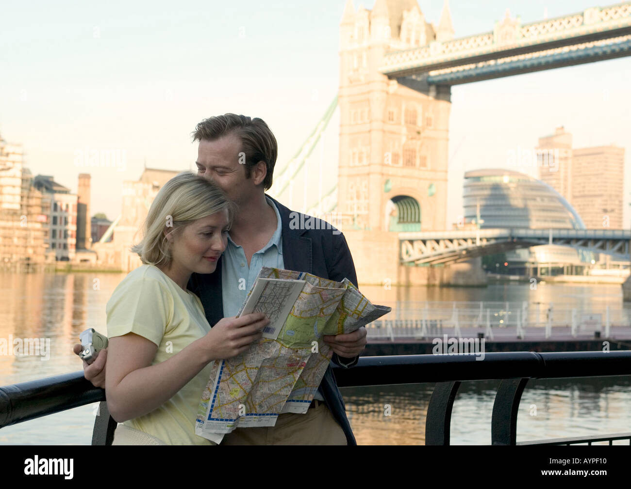 couple standing together near tower bridge looking at map in london - Stock Image
