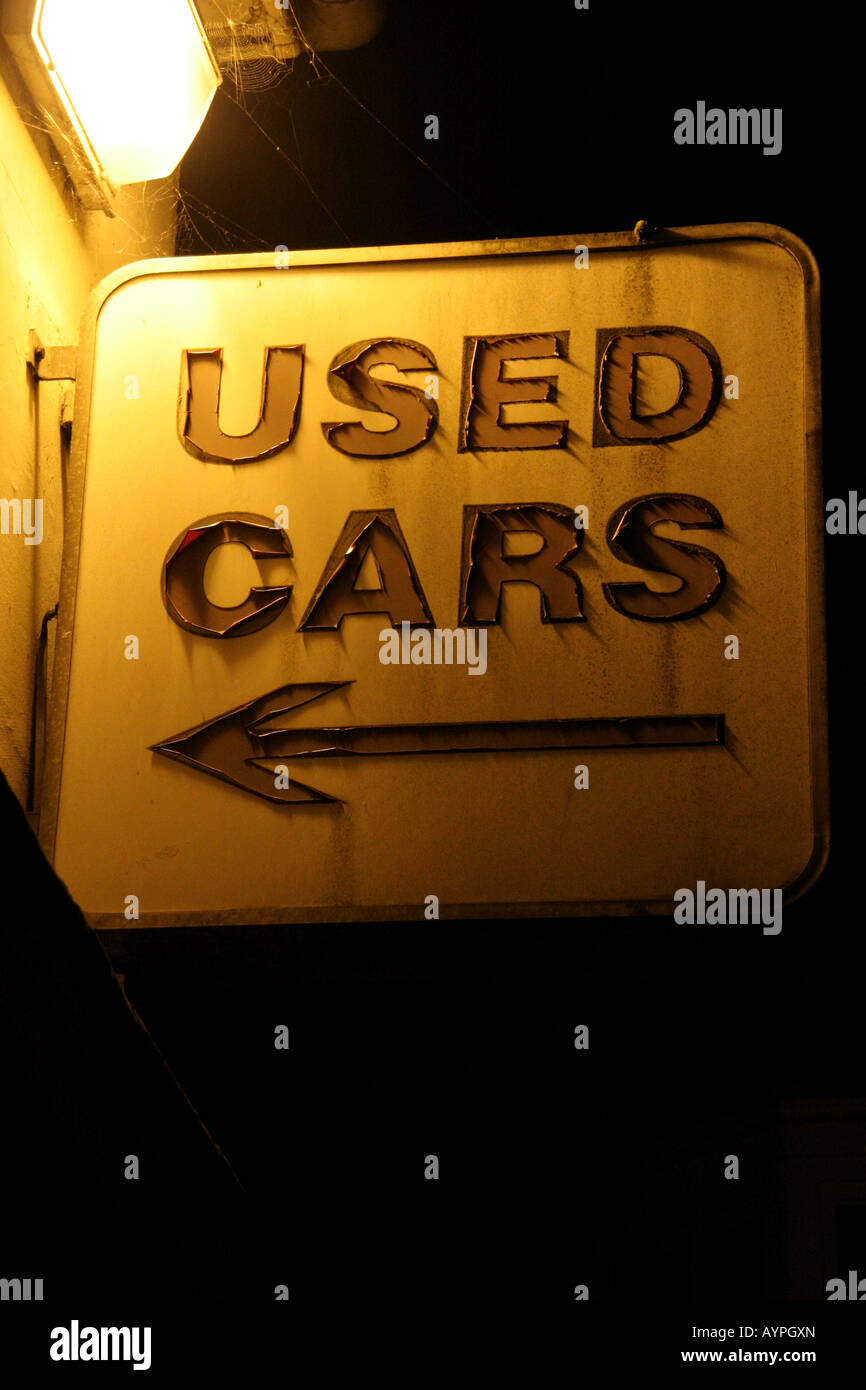 Used car sales sign showing serious signs of wear with arrow pointing left Stock Photo
