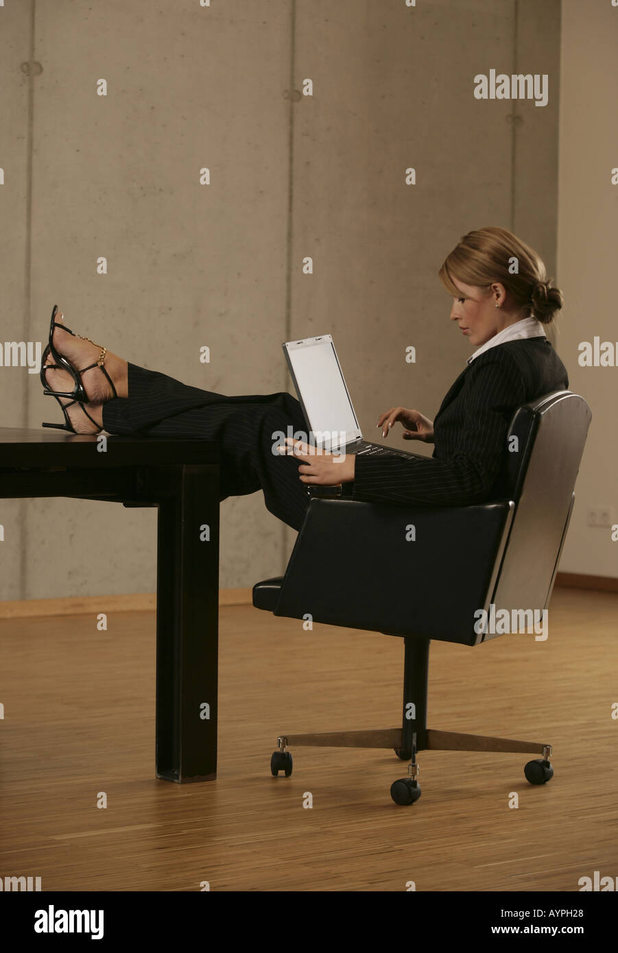 A blonde businesswoman smoking and drinking with a laptop on her lap Stock Photo