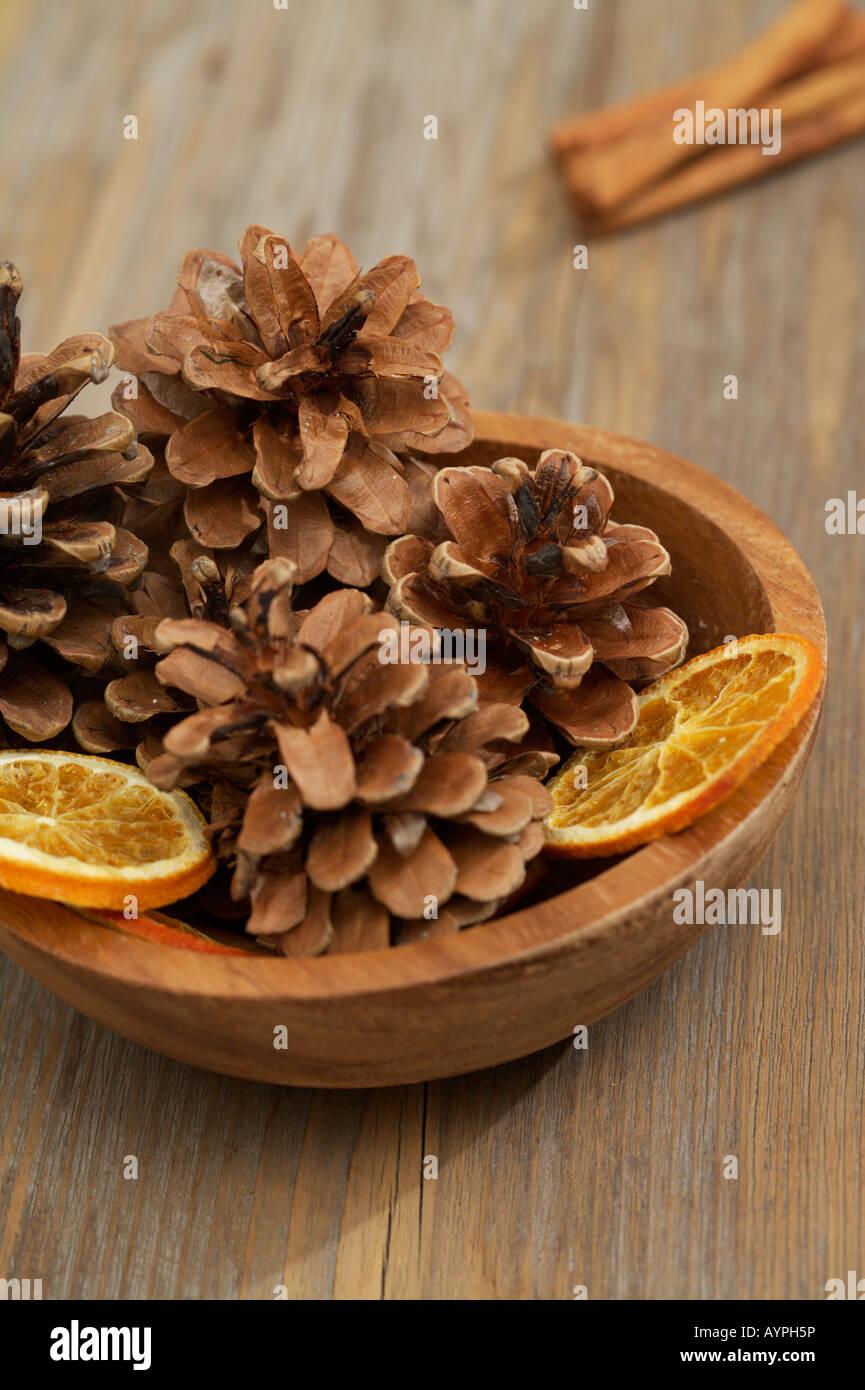 Dish with pine cones and orange slices - Stock Image