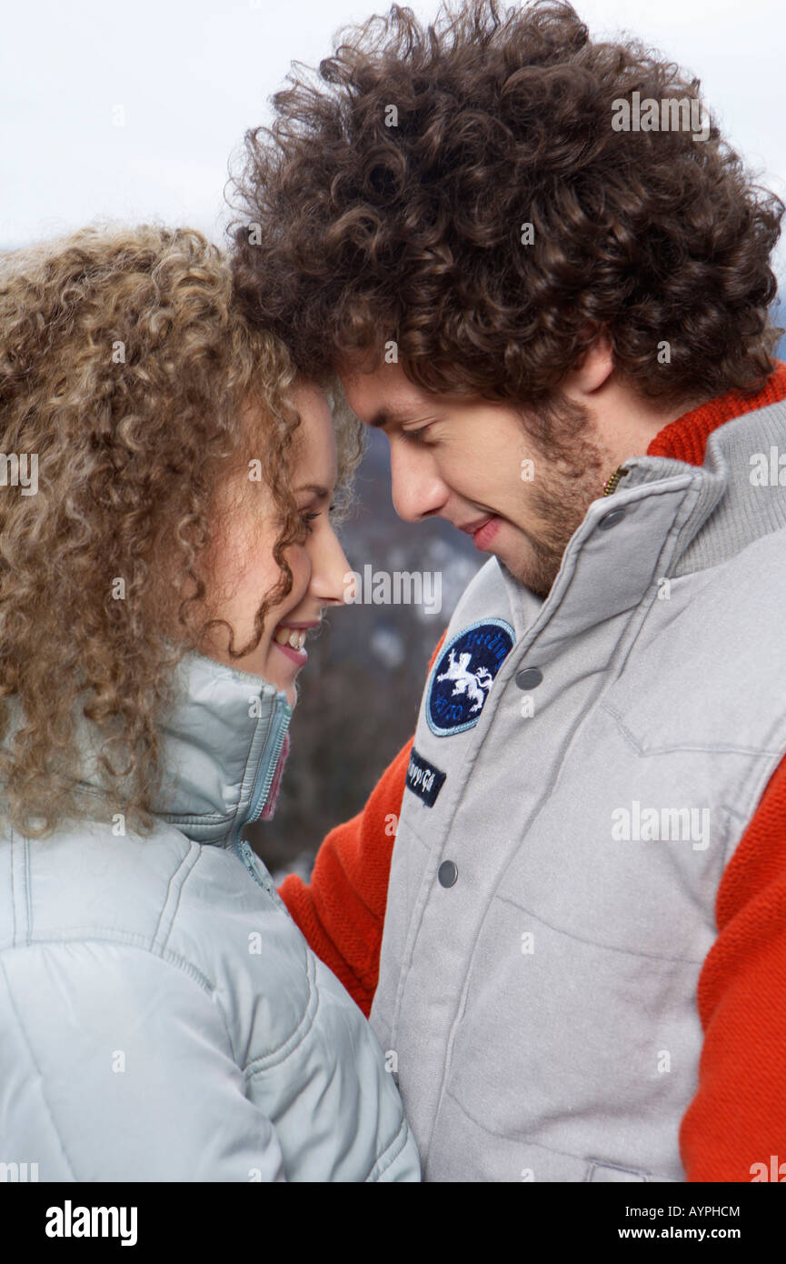 Young heterosexual couple embracing each other, close-up - Stock Image