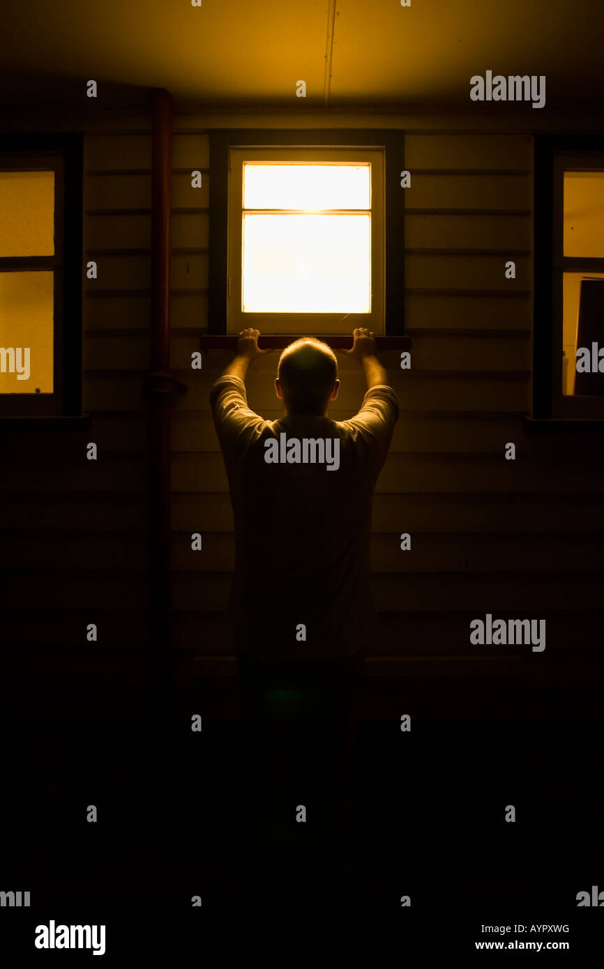 Man looks into house window at night. Full model and property release. - Stock Image