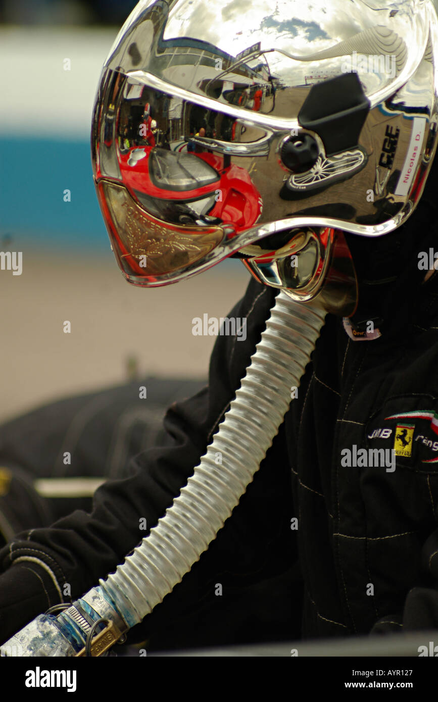 Pit crew refueling racing car with reflective helmet - Stock Image