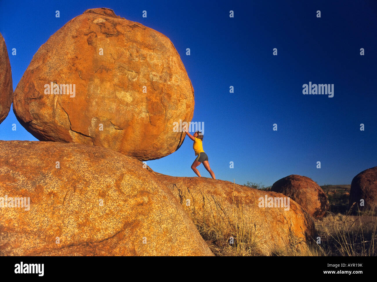 Woman propping up large round rock, Devil's Marbles, Northern Territory, Australia - Stock Image