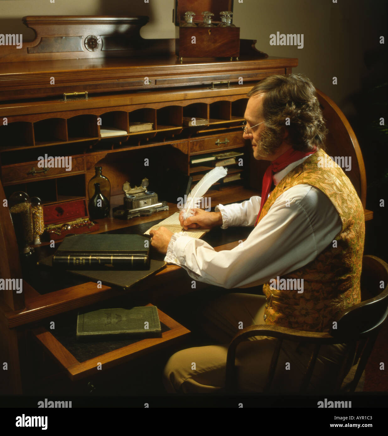 Man In 19th Century Costume Sitting At Roll Top Desk