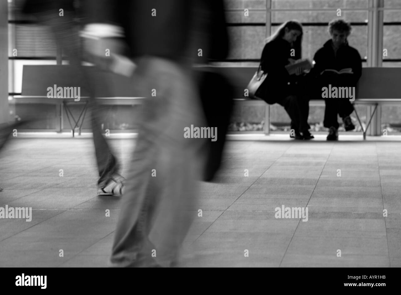 Man with a bag walking through a business  recaption - Stock Image