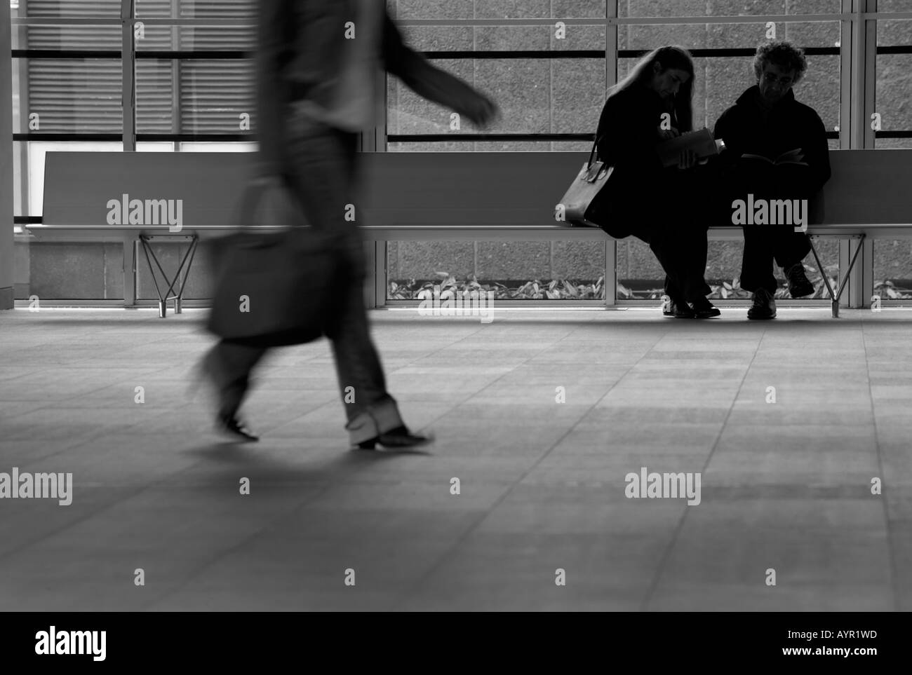 Woman with a bag walking through a business reception - Stock Image