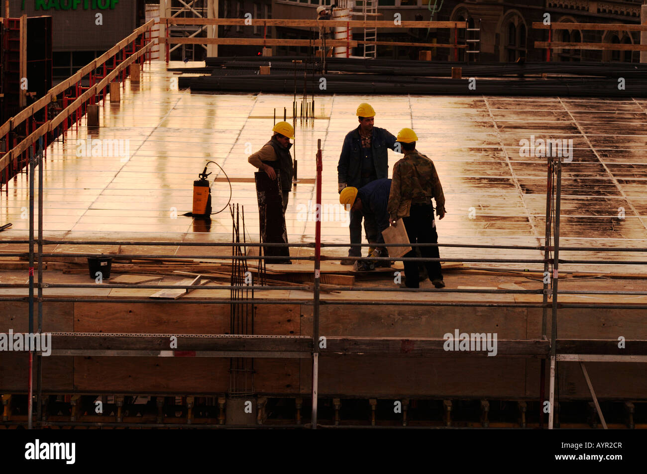 Construction workers talking at a construction site, building shell - Stock Image