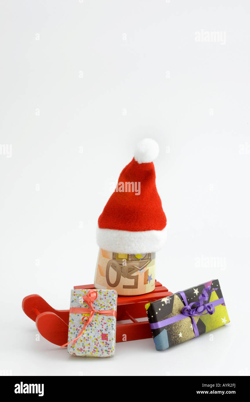 Christmas, red sleigh with 50-Euro bills rolled up, Santa hat and wrapped presents - Stock Image