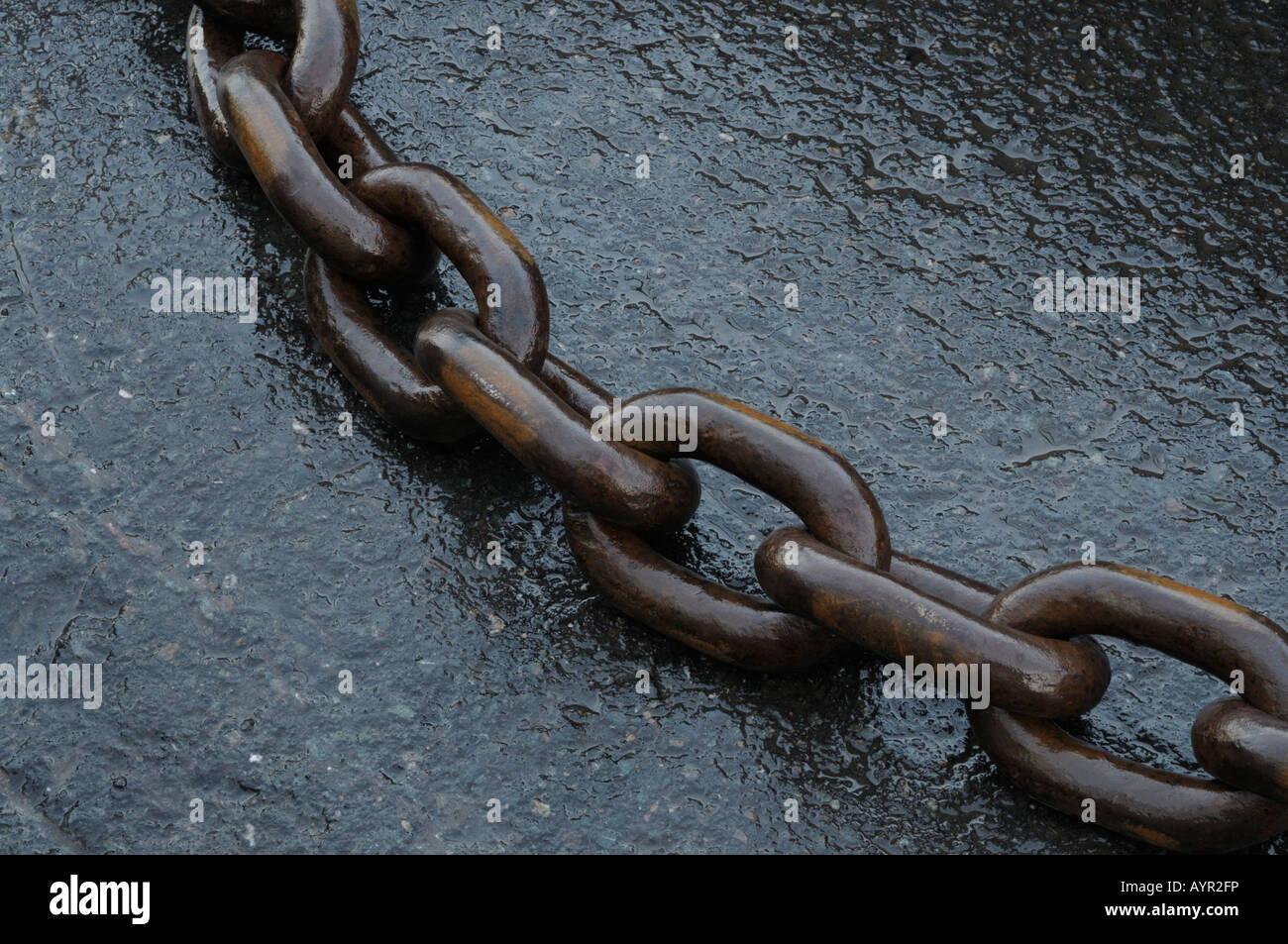 Iron chain on wet asphalt Stock Photo